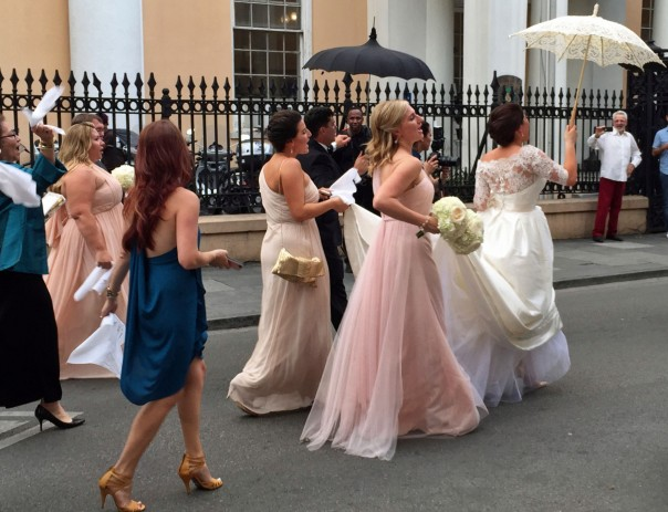 A wedding party NOLA-style; from the church to the reception, singing down the street followed by a lively brass marching band.